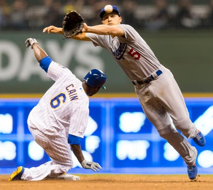 April 20: Los Angeles Dodgers shortstop Corey Seager dives for a wild throw as the Milwaukee Brewers' Lorenzo Cain slides into second base after hitting a double during the seventh inning at Miller Park. The Brewers won the game, 5-0.