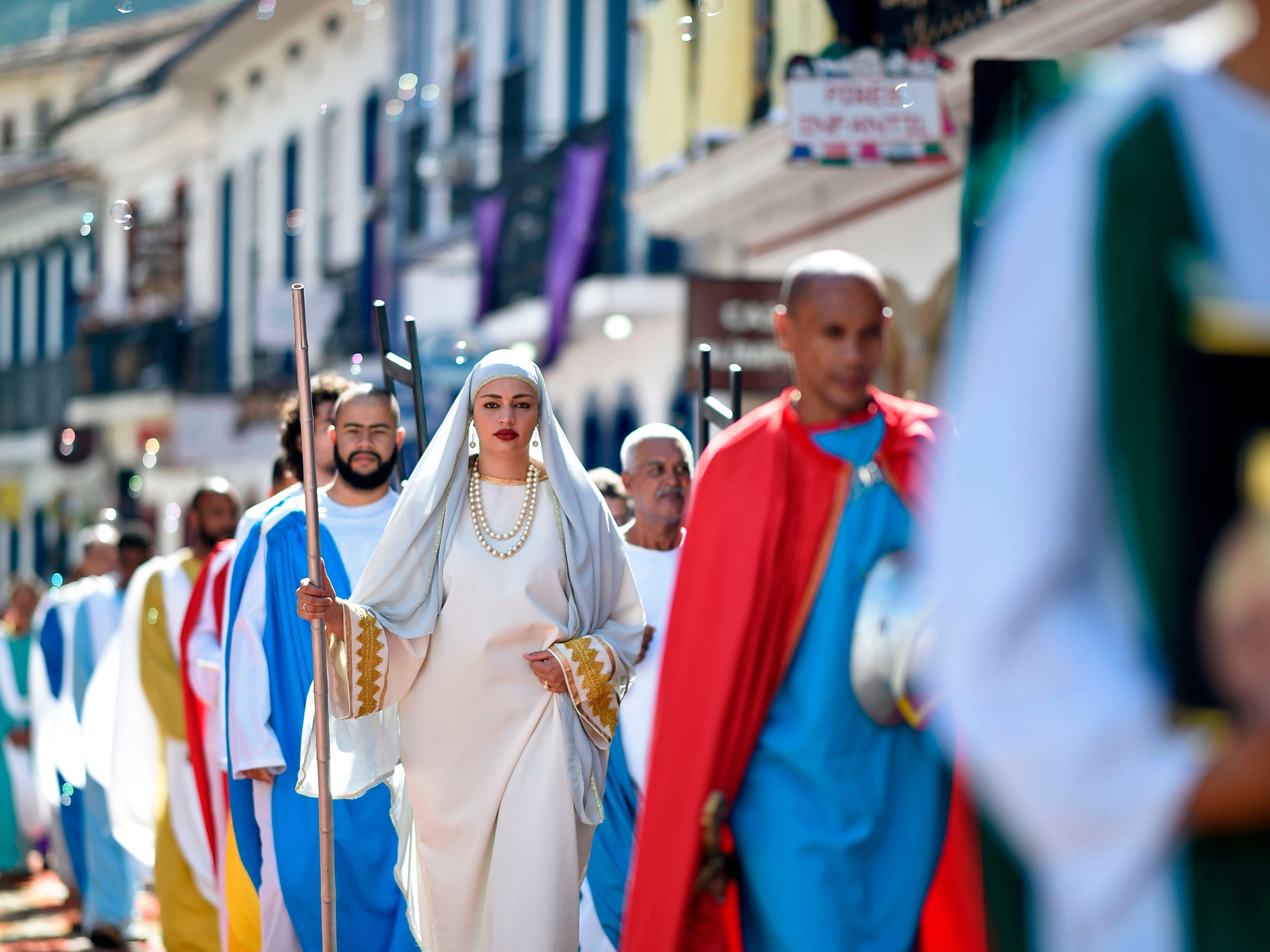 Catholics walk over a sawdust rug during an Easter procession representing the resurrection of Christ, in the Brazilian city of Ouro Preto, Minas Gerais State, on April 21, 2019. The streets are decorated by locals and tourists who use about 60 tons of colored sawdust.