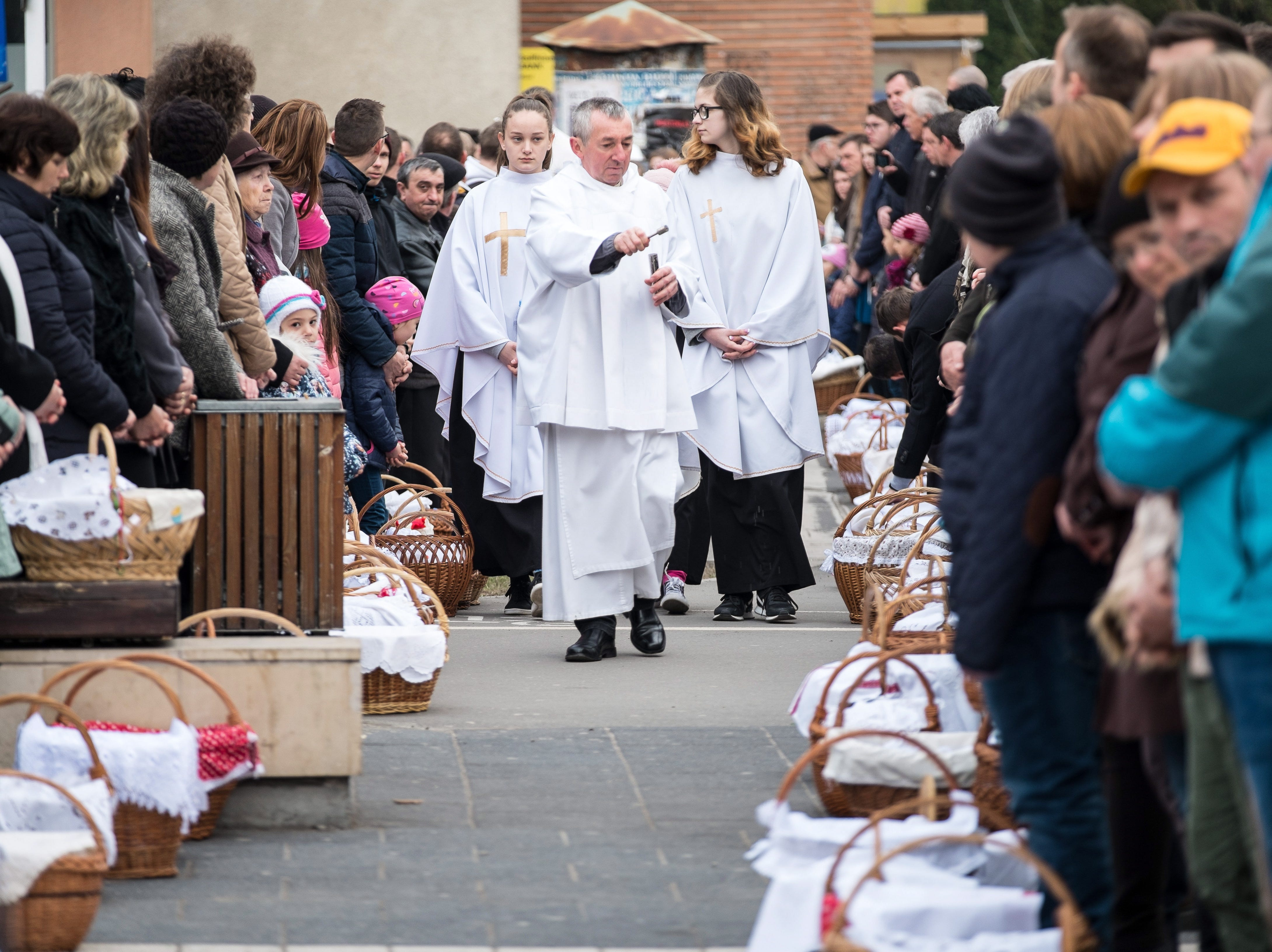 A Catholic priest blesses the Easter baskets brought by believers on Easter Sunday in the main square of Csikszereda in Transylvania, Romania on April 21, 2019.