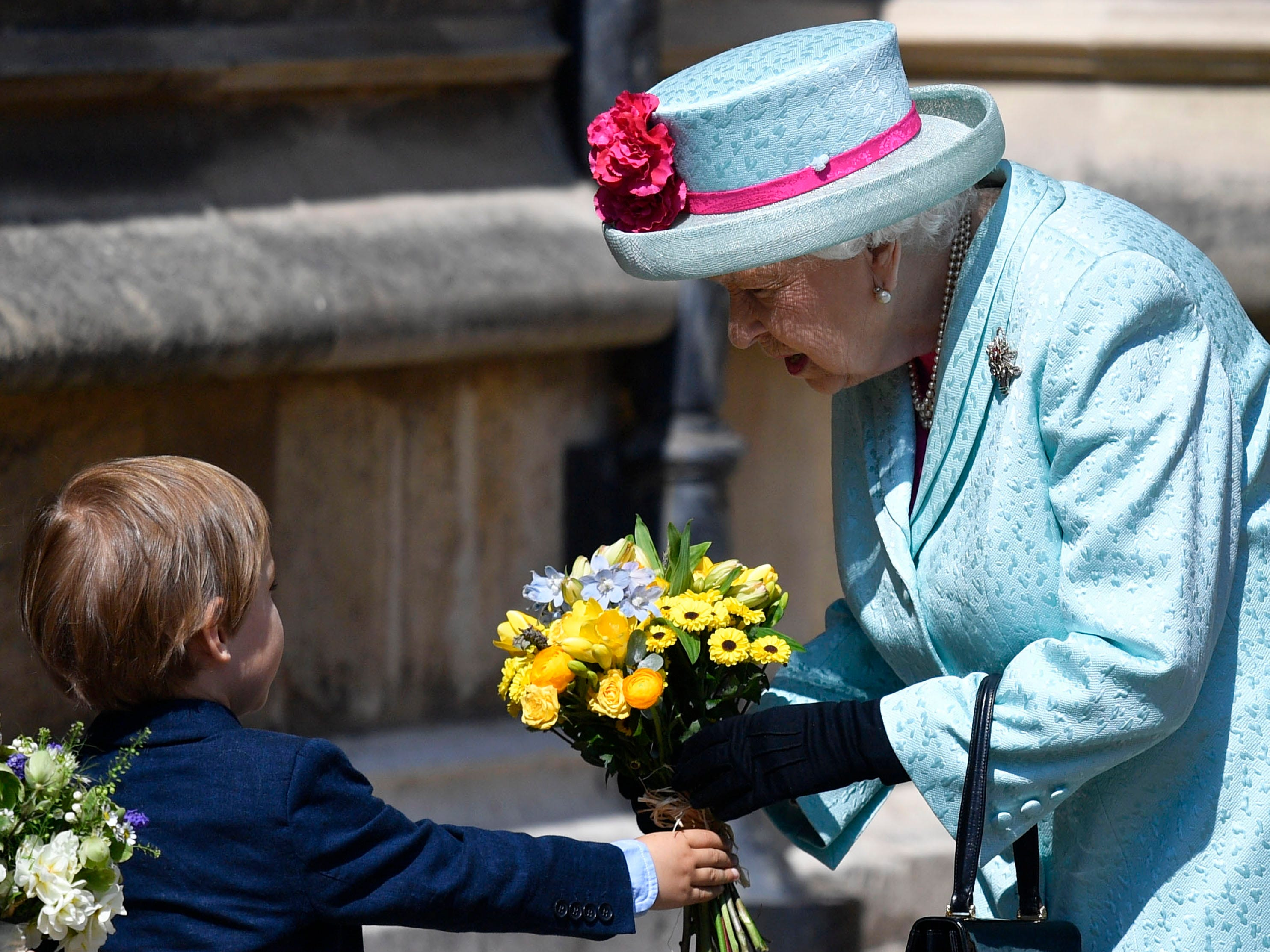 Queen Elizabeth receives flowers from a child as she leaves the annual Easter Sunday Service at St Georges Chapel in Windsor Castle on April 21, 2019. This year the service falls on the Queen's Elizabeth II birthday, who turns 93.