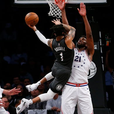 April 20: Nets guard D'Angelo Russell (1) tries to shoot over 76ers defender Joel Embiid (21) during Game 4.