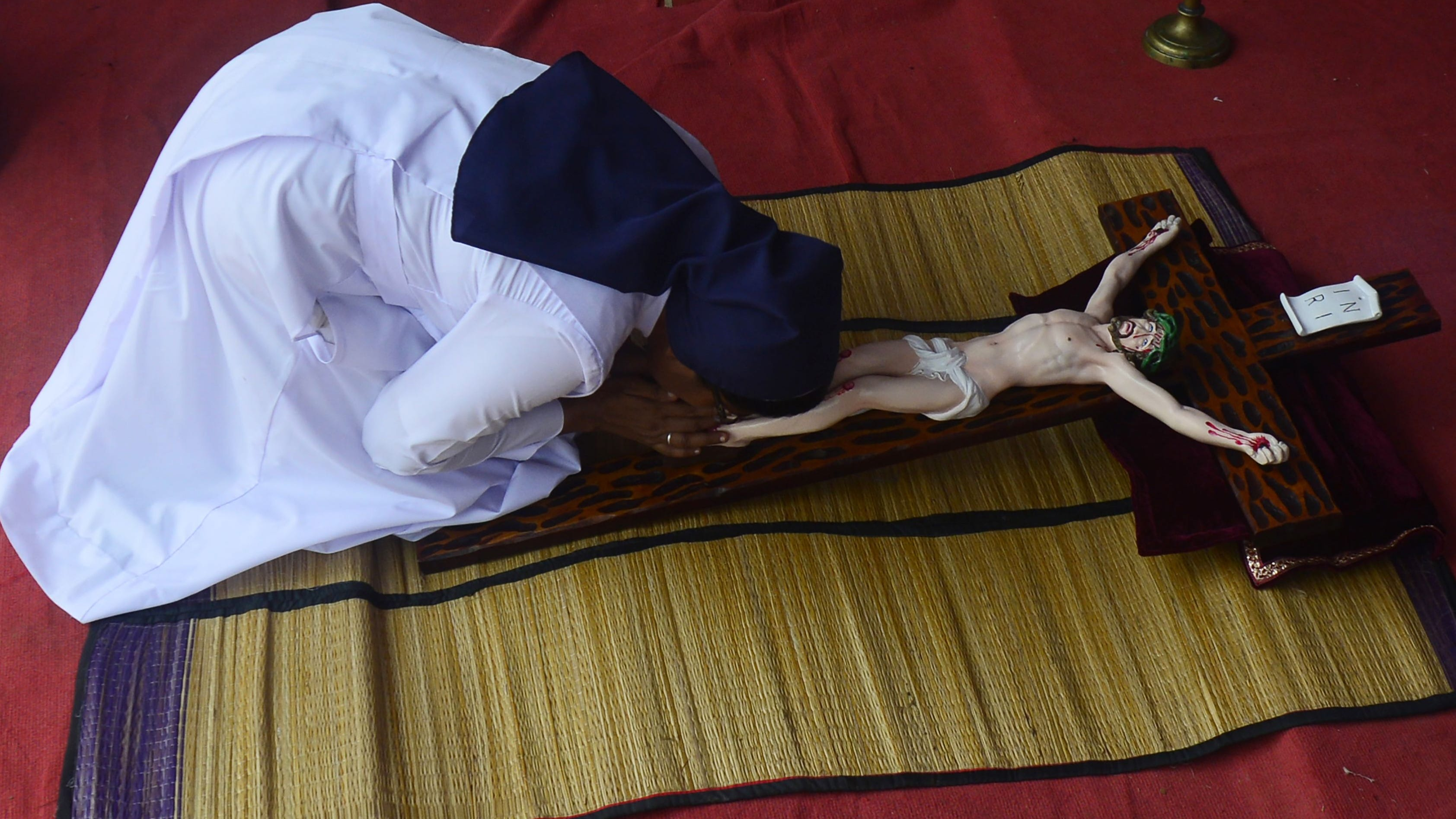 A Sri Lankan nun kisses the feet of an effigy of Jesus Christ on a cross during mass on Good Friday in Katukurunda village on April 19, 2019. Christians account for around six percent of Sri Lanka's 20 million population.