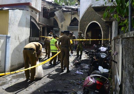 Sri Lankan security personnel and investigators look through debris outside Zion Church following an explosion in Batticaloa in eastern Sri Lanka.