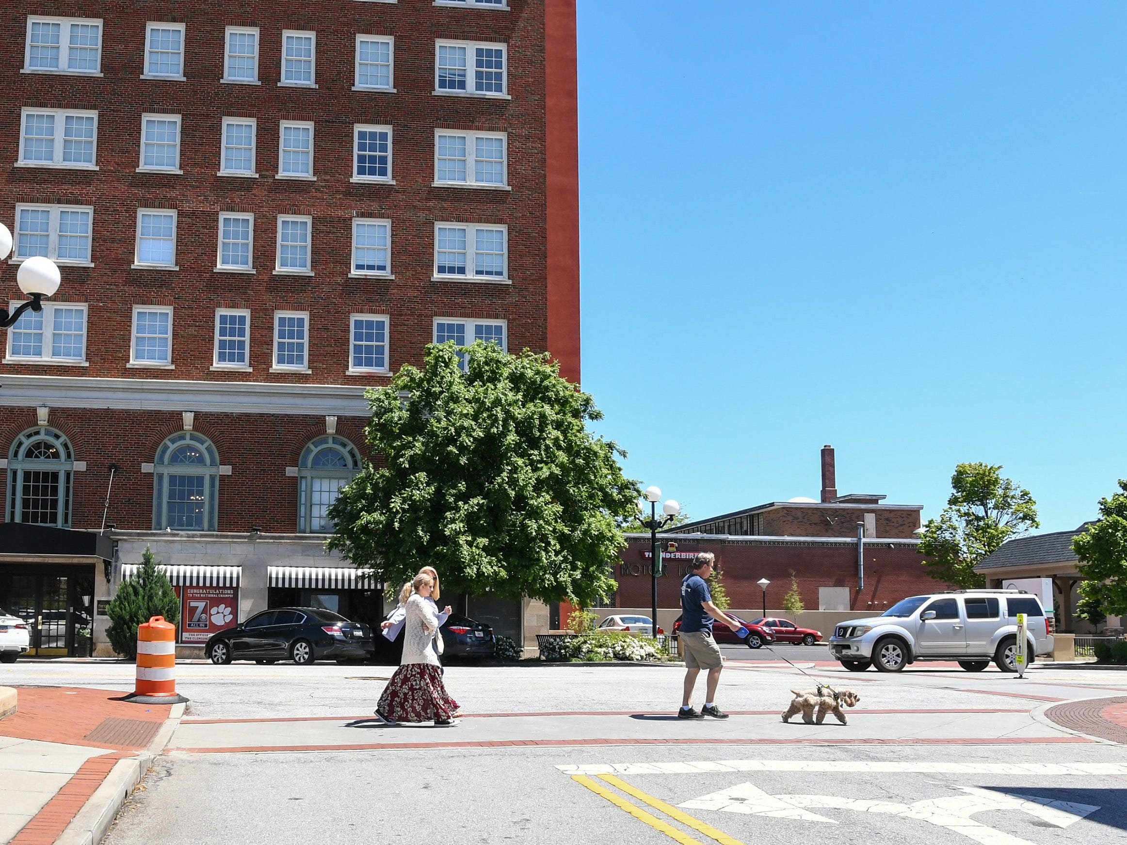 Rick and Ann Kummrow walk their dog with daughter Alexa near The Calhoun Lofts Apartments, across the street from the building they bought at 401 North Main Street in downtown Anderson. The couple pitched their plan to create The Historic Postmark Anderson, a mix of housing upstairs, retail on the main floor, and possibly a restaurant downstairs. The structure built in 1909 was previously a funeral home, and before that a United States Post Office.