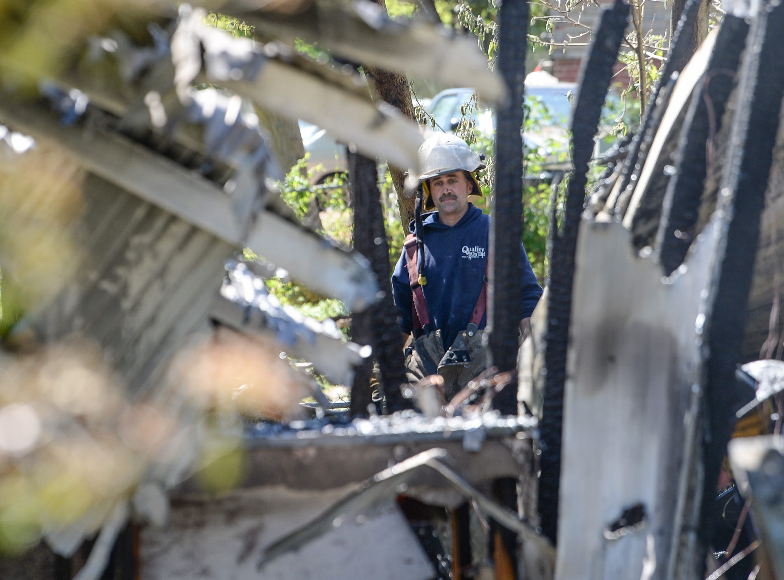 Starr firefighter Garrett Stone looks at the remains of a fire which Centerville and Homeland Park responded to on the corner of Boston and Beta Streets in West Anderson Monday. The clear skies made it possible to see the smoke from the Northeast side of Anderson County. Wendell Hunter, Anderson County fire investigator is investigating the cause as the firemen were cooling down hot spots.