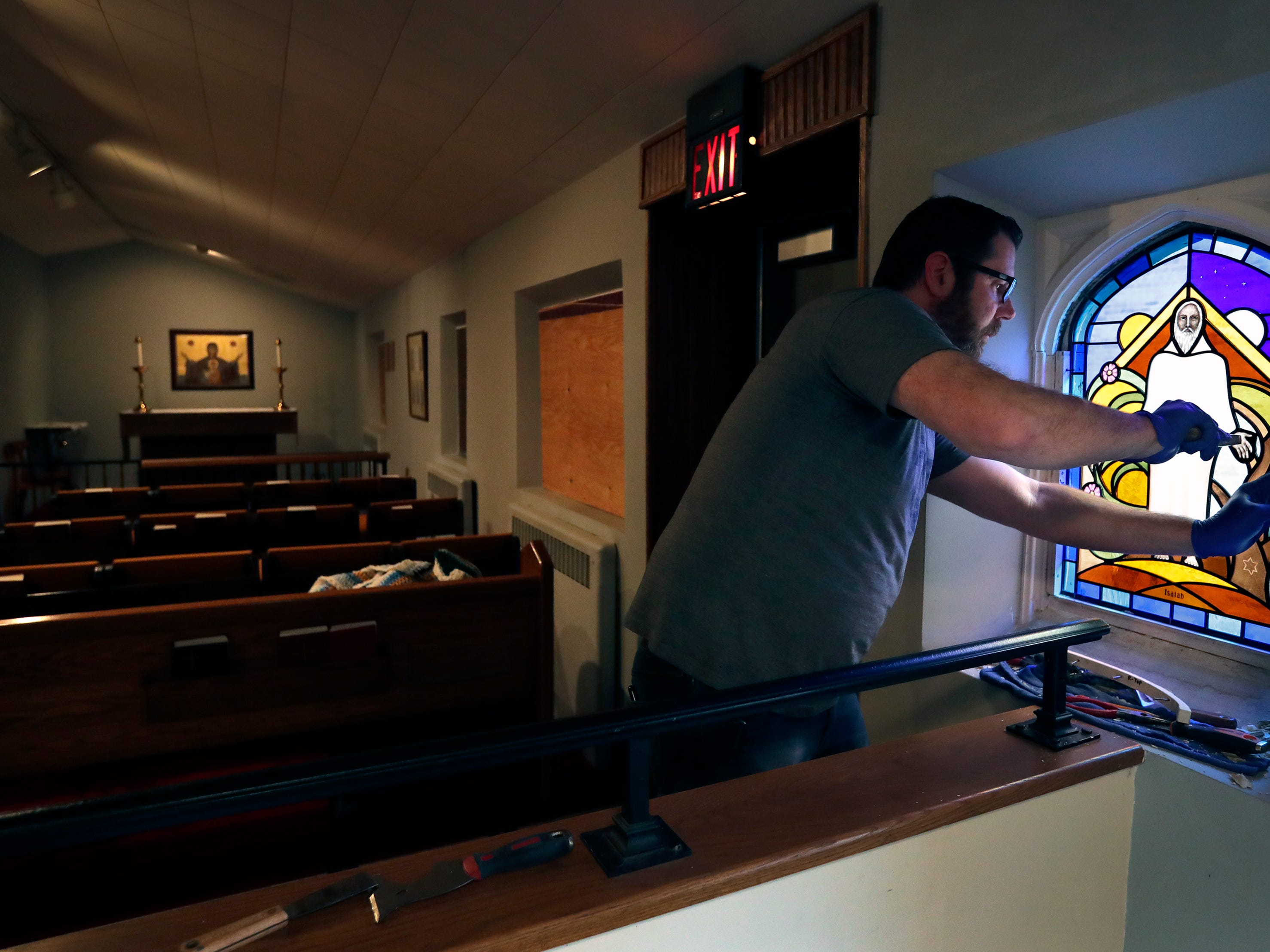 Russell Farlow, a glazier with Coventry Glassworks & Gallery, replaces a repaired stained glass window Thursday, April 18, 2019, at All Saints Episcopal Church in Appleton, Wis. The window is one of nine that were vandalized in March.Dan Powers/USA TODAY NETWORK-Wisconsin