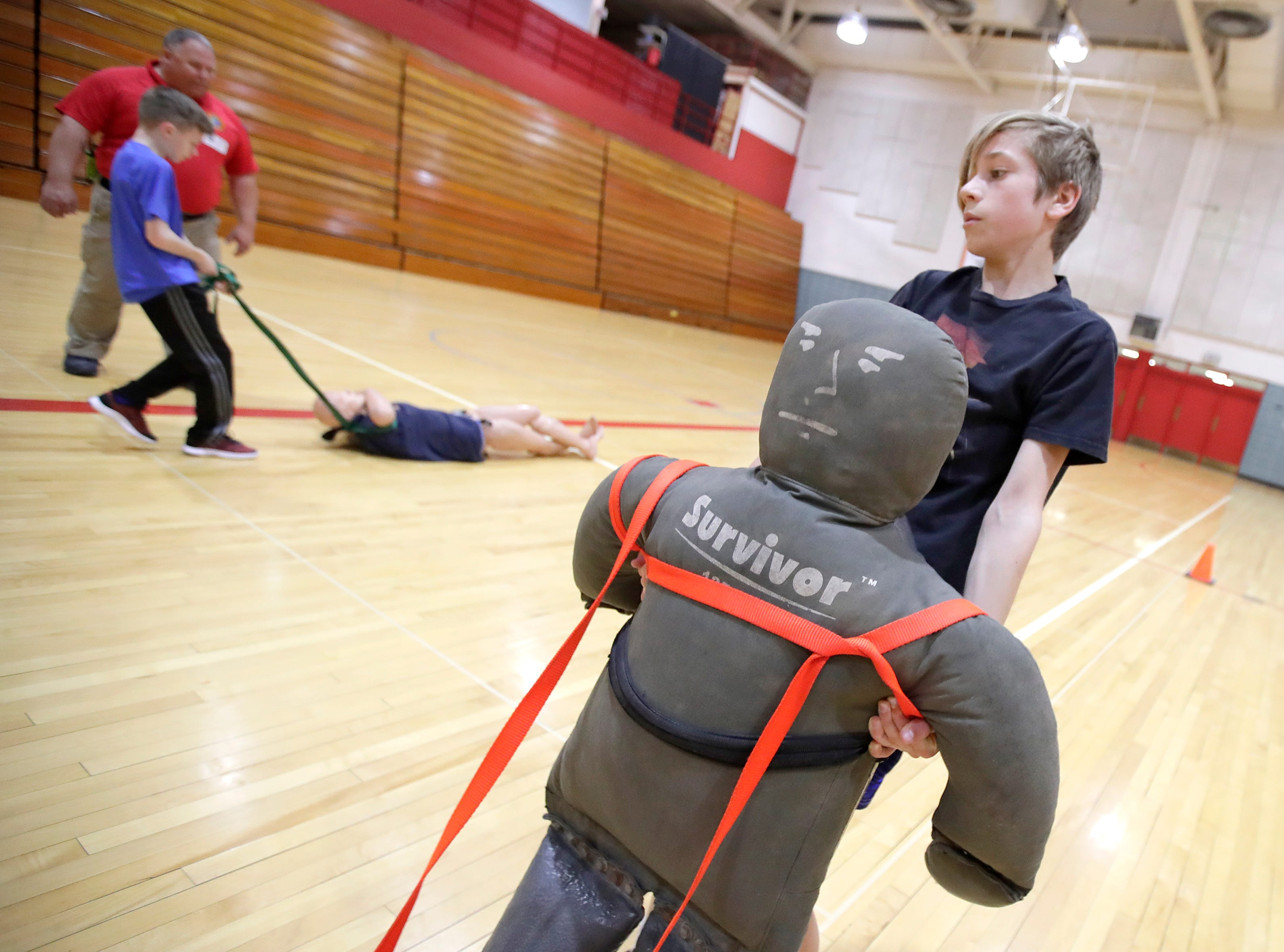 Alex Karlin, in 7th grade at Shattuck Middle School, carries a training dummy through the gym Thursday, April 18, 2019, in Neenah, Wis. Neenah-Menasha Fire Rescue ran fitness activities to show students some of the physical demands of firefighting. Danny Damiani/USA TODAY NETWORK-Wisconsin