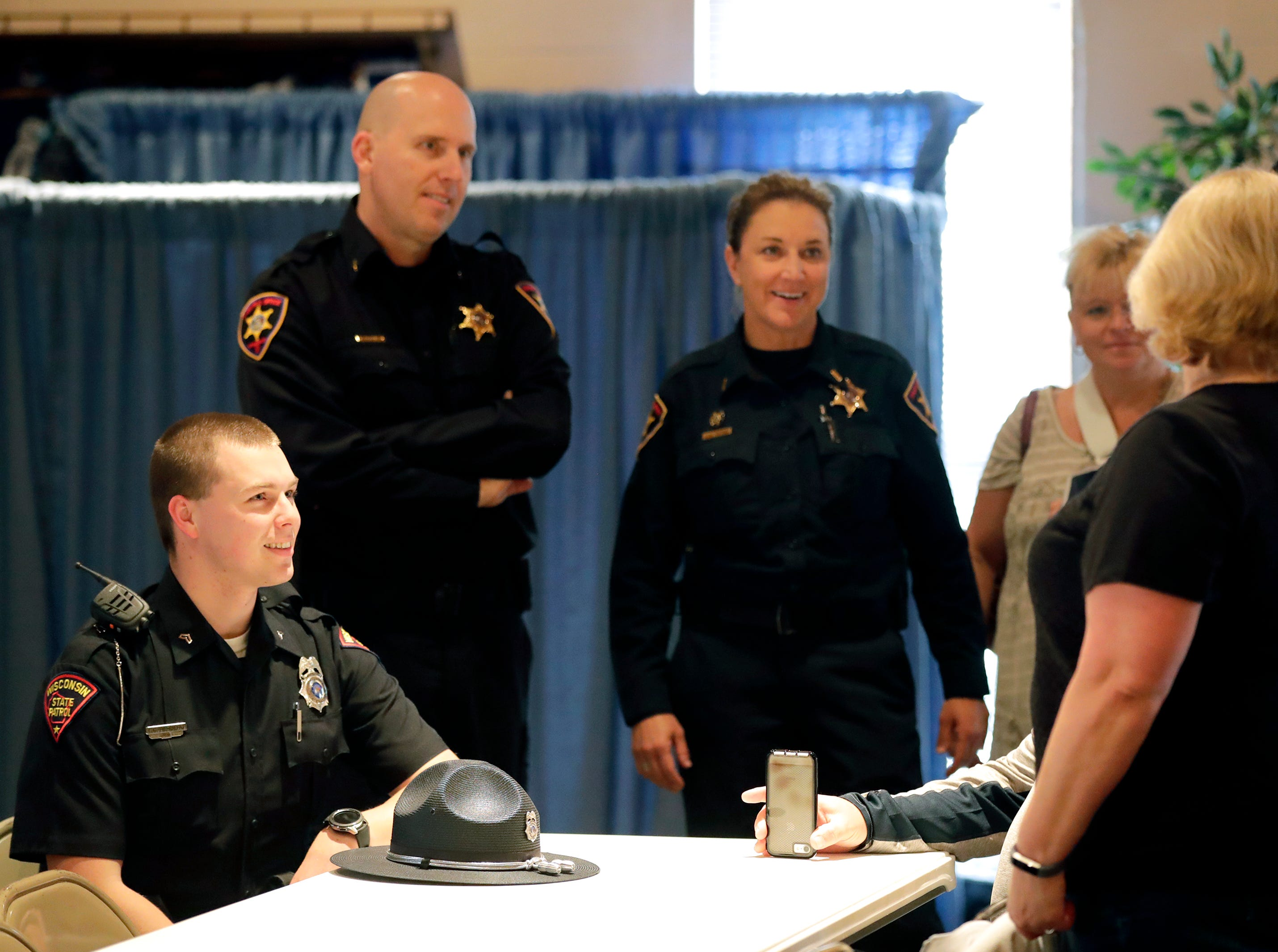 Wisconsin State Patrol Inspector Ethan Rehberg, seated, Chief Deputy Todd Christopherson and Lt. Lori Seiler, right, talk with other responders during the I-41 Mass Casualty Incident of Feb. 24, 2019 Recognition Event Tuesday, April 16, 2019, at Gloria Dei Lutheran Church in Neenah, Wis. Christopherson and Seiler are with the Winnebago County Sheriff's Department.Dan Powers/USA TODAY NETWORK-Wisconsin