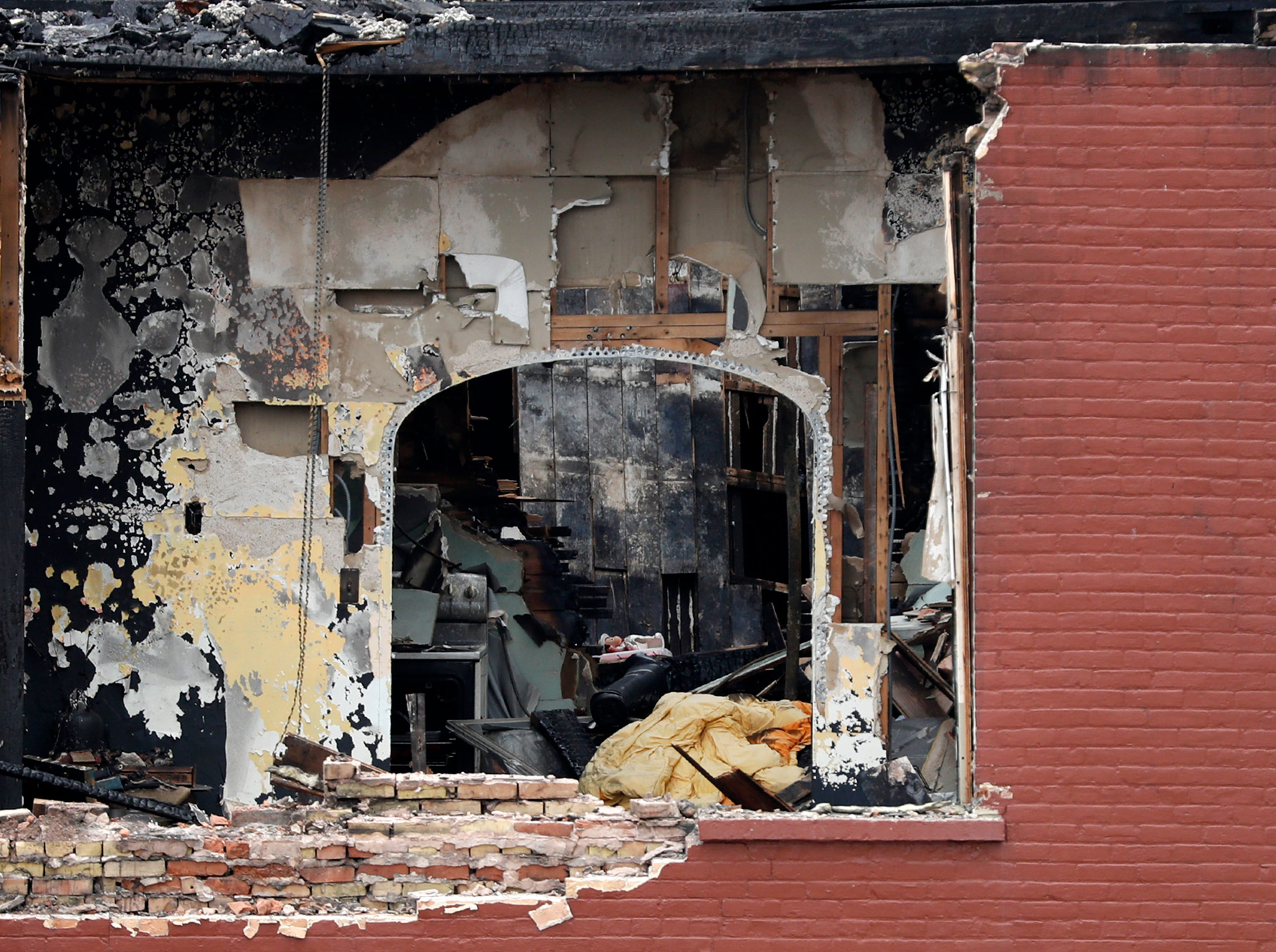 Fire damaged apartments are visible as demolition begins on the building that housed Author's Kitchen and Bar and apartments on the corner of West Washington and North Appleton Streets Monday, April 22, 2019, in Appleton, Wis. 