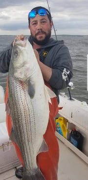 Matt Calabria of Hazlet holds up a 51-pound bass his father Hector Calabria landed on Easter Sunday. Matt Calabria said the fish was released.
