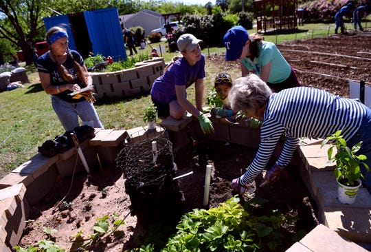 Church members plant a raised bed at the Open Door Community Garden. Located at S.19th and Amarillo streets, produce grown by the garden is available to anyone.