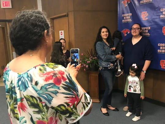 Dolores Palacios, left, takes a photo of her daughters Carolina and Estrellita during Cooper High School's reveal of its Top 25 students of the Class of 2019. Estrellita Palacios ranked 11th and will attend Hardin-Simmons University to study nursing after graduation in May.