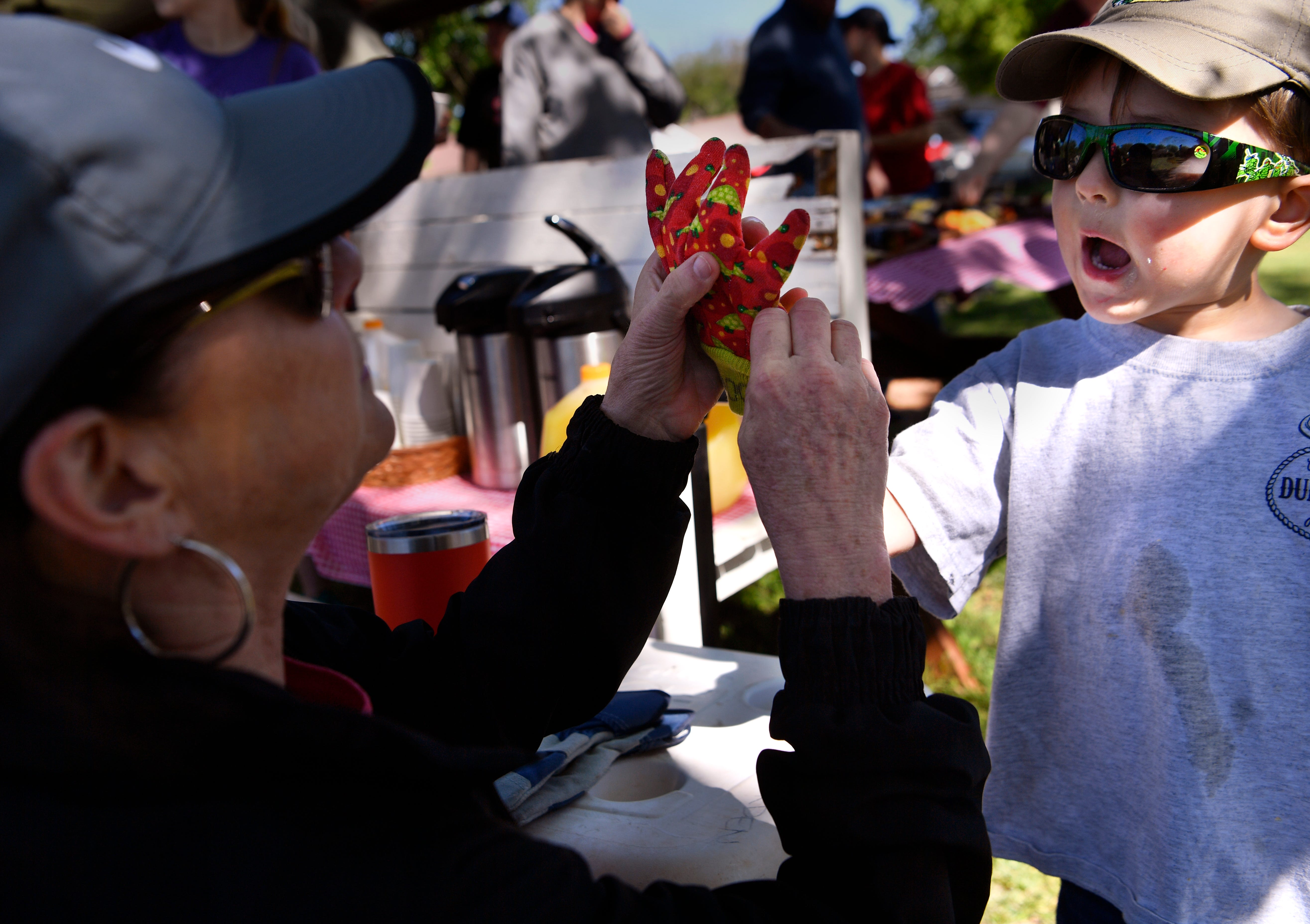 Lora Brinkman tries for the second time to get a glove on the hand of her 3-year-old grandson, Royce.