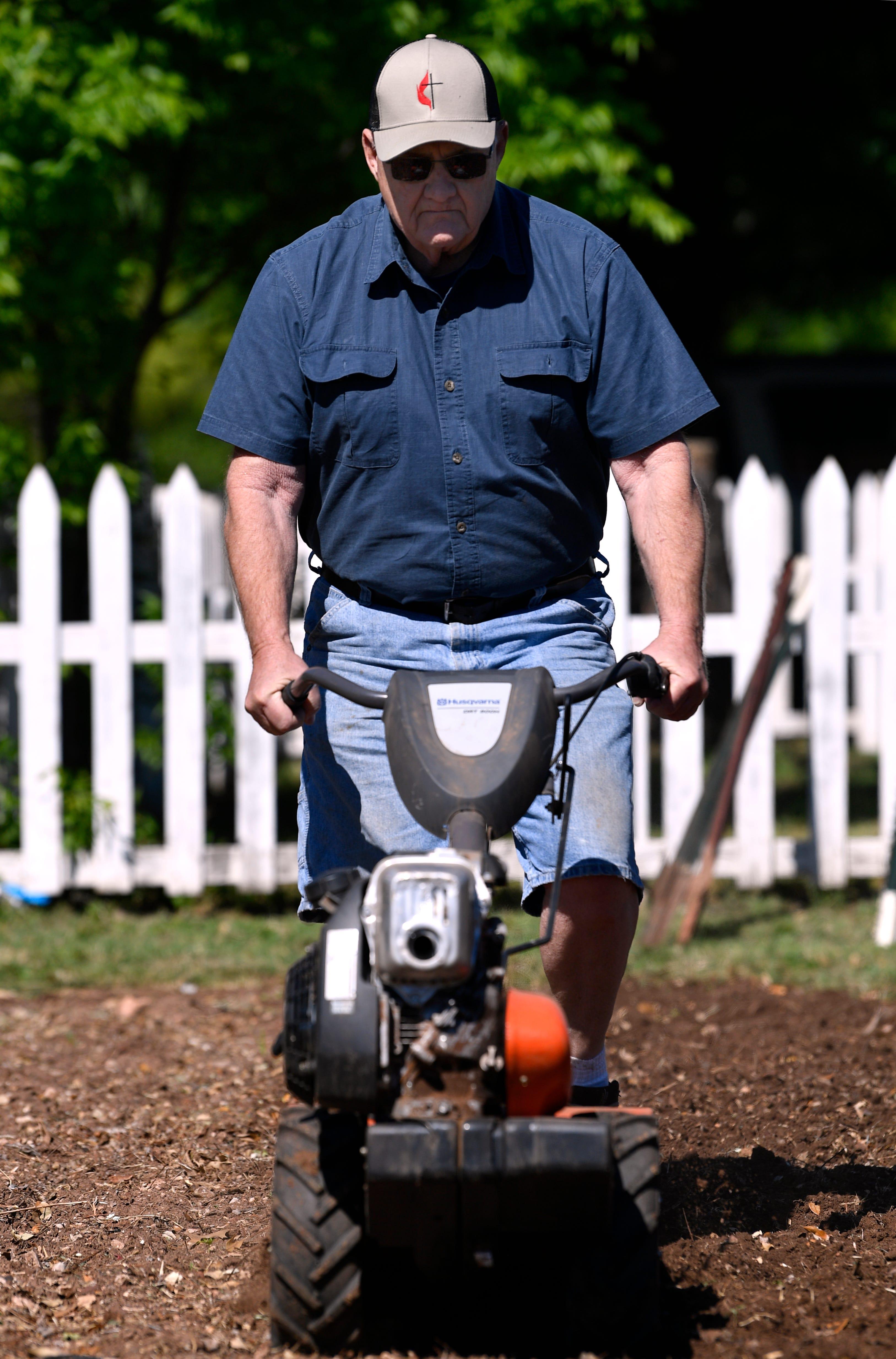 Carlton Villers runs a roto-tiller Saturday as volunteers ready the Open Door Community Garden from planting.