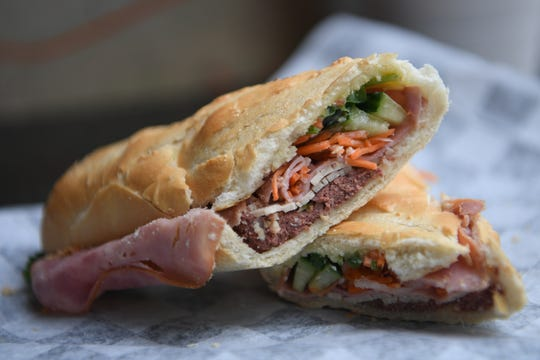 The Aloha banh mi at Aloha Cafe is a sandwich with pork loaf, sliced ham, homemade aioli, cucumbers, cilantro, jalapeno slices, picked daikon and carrots.