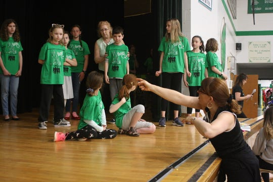 """Shannon DeAnegelo (bottom right) gives direction to students during an April 22 rehearsal of the Catholic Schools of Broome County's production of """"The Wizard of Oz."""""""