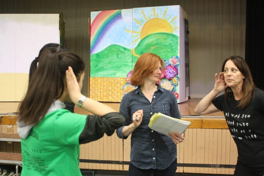 """Heather Shaffer (in blue) and Lynette Shear (in black) teach sign language to students in Broome County Catholic Schools production of """"The Wizard of Oz"""" during an April 22 rehearsal."""