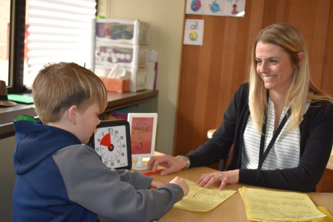 Olalla Elementary second-grade teacher Holly Winderl works with a student on reading. Winderl wishes all children could unlock the power inside them to make a difference, big or small.