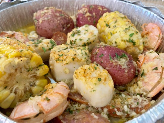 Shrimp and scallops swim in a buttery sauce with potatoes and corn in this take-out container from Melbourne Seafood Station.