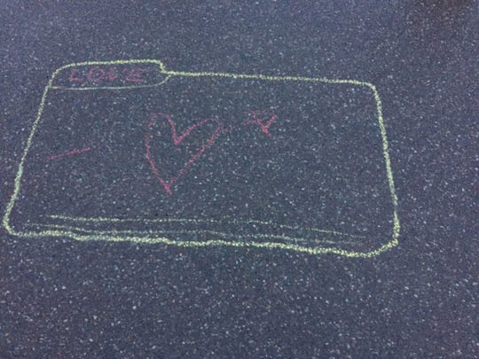 A file folder drawn in chalk rests on the parking lot near the world's tallest filing cabinet in Burlington on April 19, 2019.