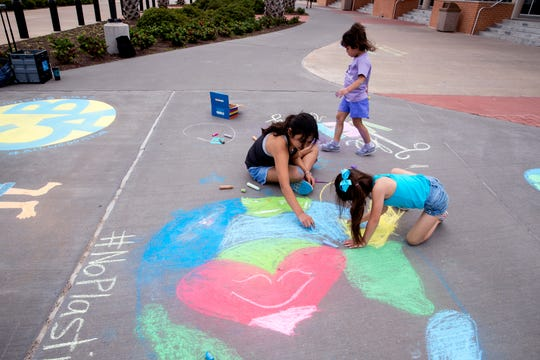 Sisters Adelina, 10, clockwise from left, Ariana, 4, and Alessandra Vela, 6, create chalk murals at Texas A&M University-Corpus Christi for Earth Day as the university kicks off a weeklong Earth Week on Monday, April 22, 2019.