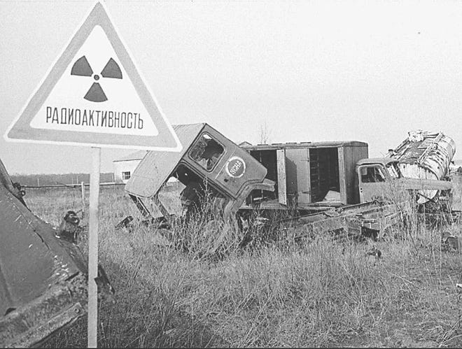 Trucks polluted by radioactivity lie abandoned in 1996 along the road to the Chernobyl nuclear plant, 6 miles away.