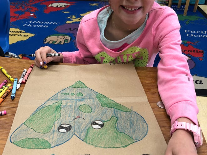 Second-grade student Gia Carroll working on her Earth Day Kroger bag.