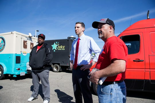 Anton Gaffney, of Sweets and Meats BBQ, left, P.G. Sittenfeld, city council member, and Anthony Lange, president of the Queen City Mobile Food Truck Association discuss final plans for The Cove Food Park on Monday April 22, 2019. Cove Food Park, Cincinnati's premier food truck park will open May 3rd at 4601 Kellogg Avenue. The new food truck park will be open Tuesday - Sunday 11 am - 11 pm and will also have covered dining, pop up shops, craft beer/wine, farmer's market and more. Photo shot Monday April 22, 2019.