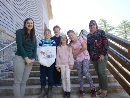 Teachers Marissa Mizeski (left) and Britt Boynton (right) pose with fourth grade students (left to right) Callen LeVasseur, Collin Russ, Dylan Auerbach, and Franki Meyer as well as the reusable bag they created.