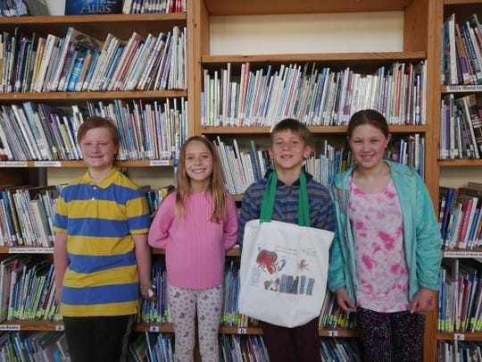 Willow School fourth graders (left to right) Collin Russ, Dylan Auerbach, Callen LeVasseur, and Franki Meyer pose with the reusable bag they designed and sold, with proceeds benefitting environmental group 4Ocean.