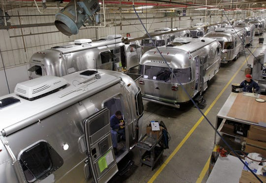In this Oct. 22, 2014 photo, Airstream travel trailers line the factory floor as they are assembled at the Airstream factory in Jackson Center, Ohio. Not only are the Airstream trailers still being built by hand at the same western Ohio site that has produced them for the past 60 years, but the company also can't roll them out of there fast enough to meet the demand these days. (AP Photo/Jay LaPrete)