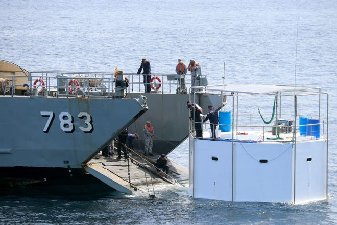 A Royal Thai Navy ship pulls a floating living platform to shore after dismantling and removing it from the sea off the coast of Phuket.