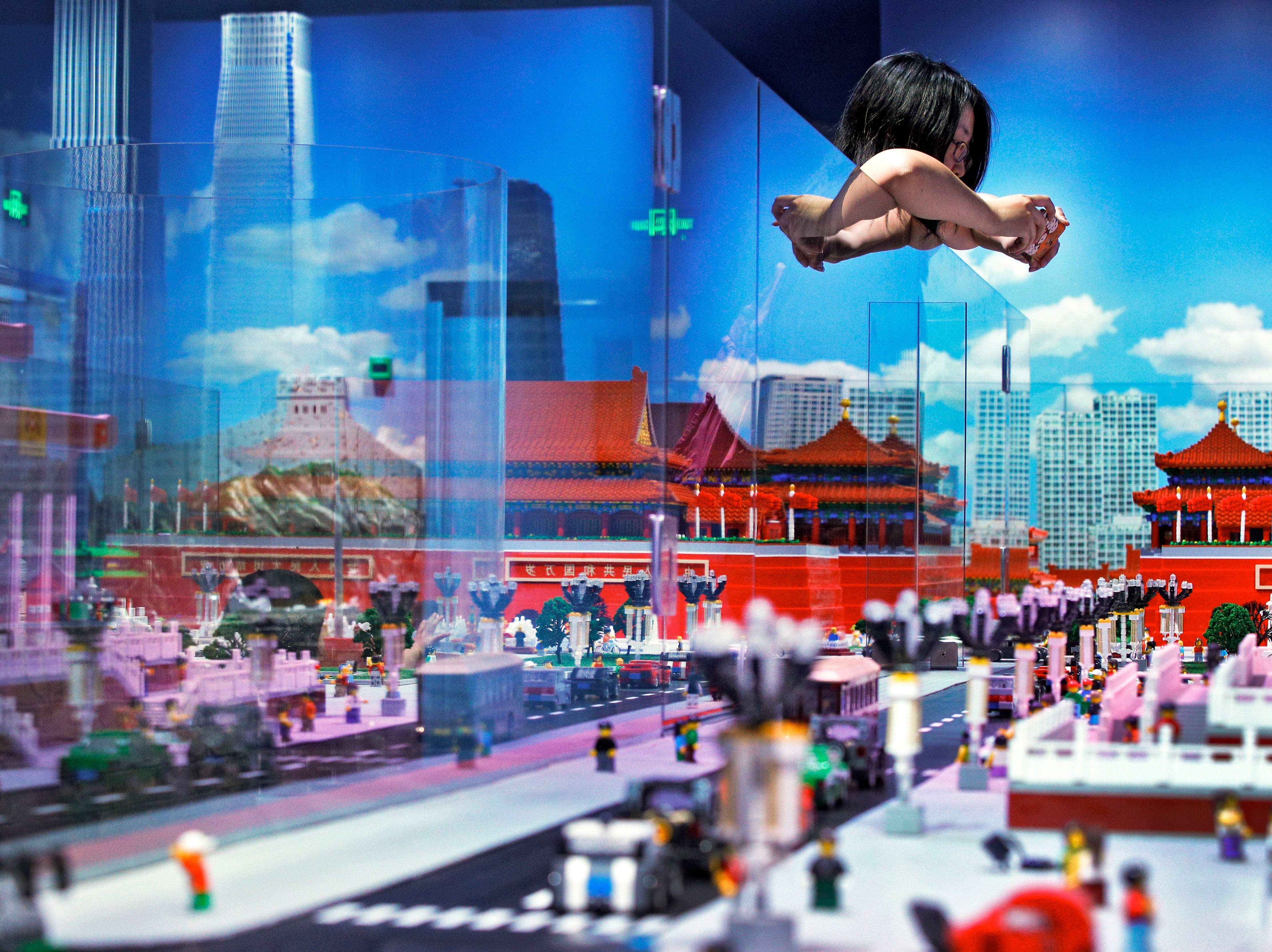 A woman takes a photo of the Forbidden City model as a glass panel reflecting the skyscrapers at the Central Business District and the Great Wall of China, all made of Lego bricks, on display at a newly opened Legoland Discovery Center in Beijing, Monday, April 22, 2019. The Legoland Discovery Center offering children and parents a sneak peek of miniatures showcases the major landmarks from historical sites to iconic skyscrapers in the capital city.