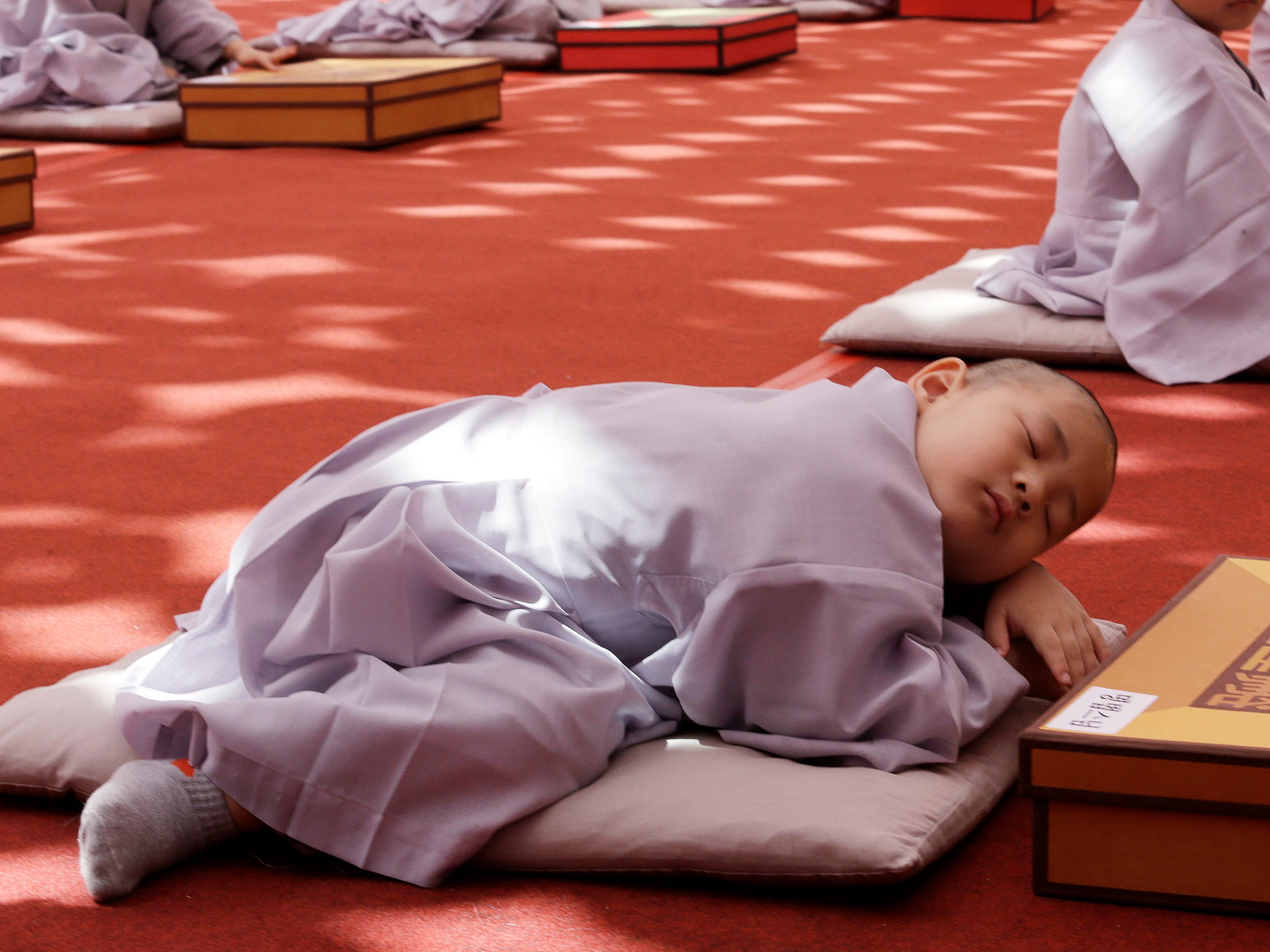 A boy whose Buddhist name is Myung Bub naps after having his head shaved during a service to celebrate Buddha's upcoming 2,563th birthday on May 12, at the Jogye Temple in Seoul, South Korea, Monday, April 22, 2019. Myung Bub is one of the 10 children who entered the temple to have an experience of monks' life for three weeks.
