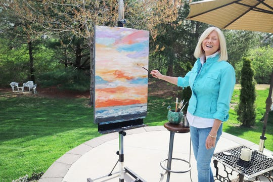 """Kansas City, Mo., artist Jan Fellers enjoys the sunshine while painting outside her studio. This piece is called """"Marmalade Sky."""""""