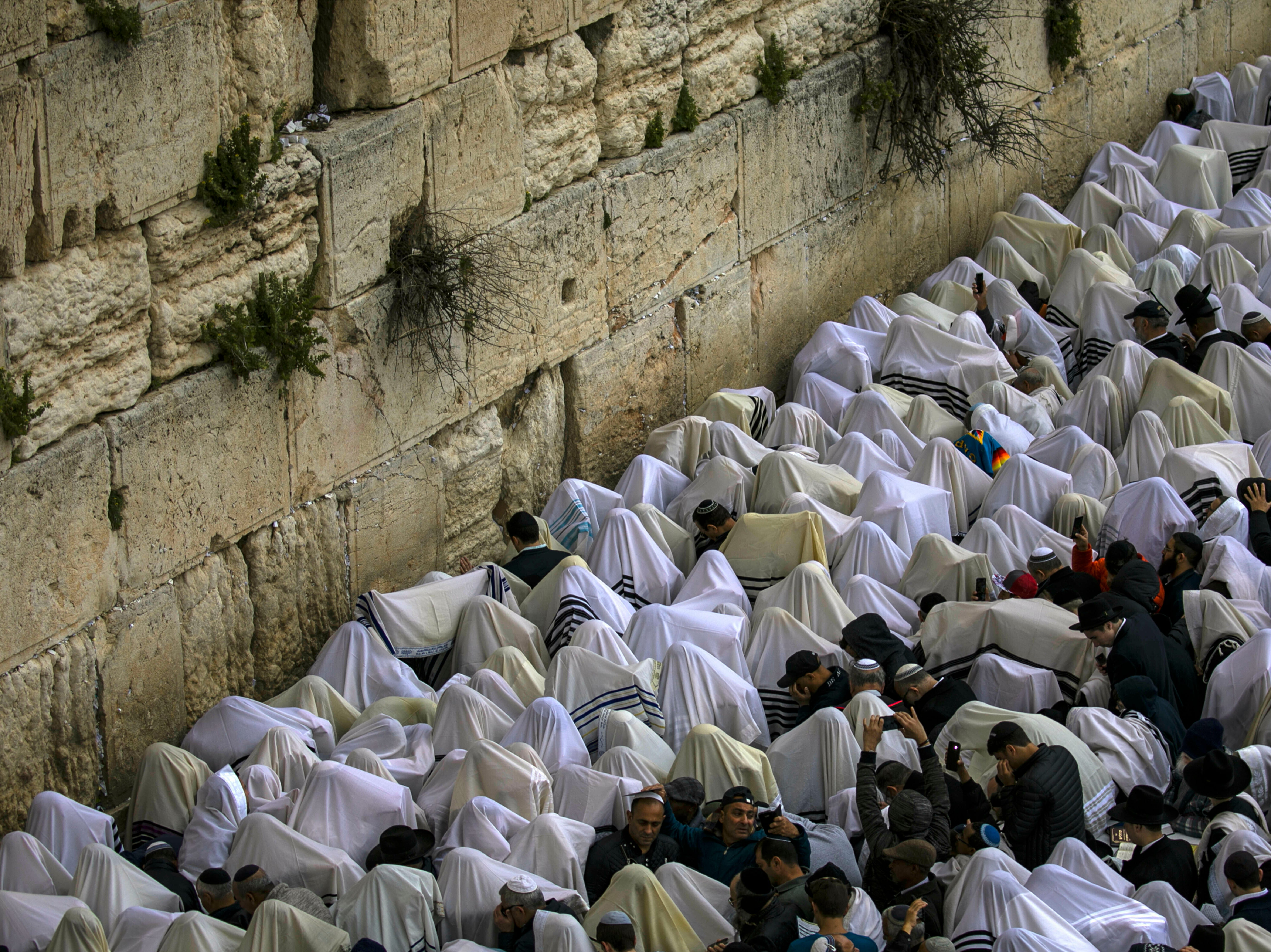 Covered in prayer shawls ultra-orthodox Jewish men of the Cohanim priestly caste participate in a blessing during the Jewish holiday of Passover, at the Western Wall, the holiest site where Jews can pray in Jerusalem's old city, Monday, April 22, 2019.