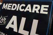"""In this April 10, 2019 file photo, a sign is shown during a news conference to reintroduce  """"Medicare for All"""" legislation, on Capitol Hill in Washington."""