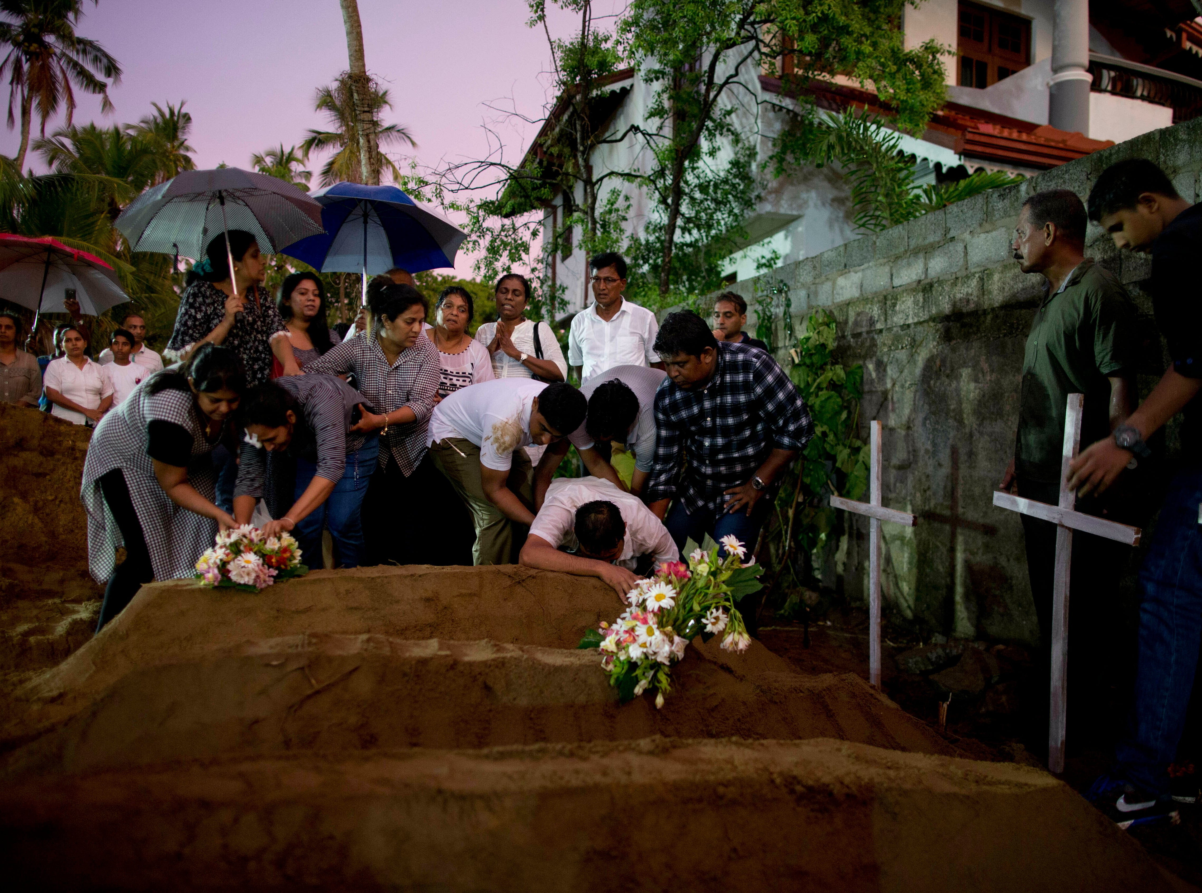 Relatives place flowers after the burial of three victims of the same family, who died at Easter Sunday bomb blast at St. Sebastian Church in Negombo, Sri Lanka, Monday, April 22, 2019. Easter Sunday bombings of churches, luxury hotels and other sites was Sri Lanka's deadliest violence since a devastating civil war in the South Asian island nation ended a decade ago.