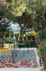 A playful pattern of check and flowers is underfoot in this charming setting with colorful bistro furniture. The Oaxaca design by Nani Marquina is part of the first collection of outdoor rugs for the eponymous Spanish brand Nanimarquina.
