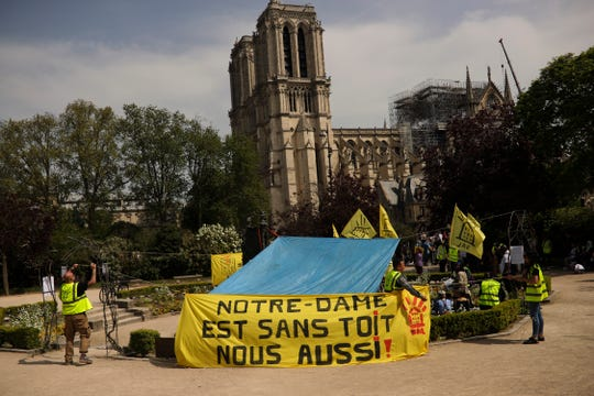 "People fix a banner that reads in French: ""Notre-Dame is roofless, we too!"" during a protest in front of the Notre Dame cathedral in Paris, Monday, April 22, 2019."