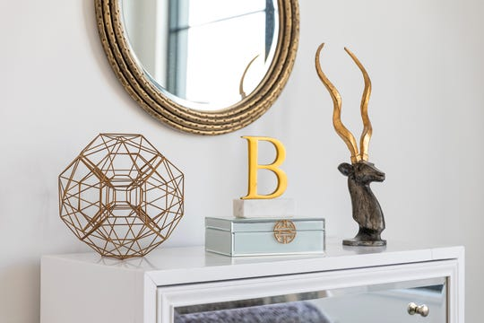 Gold and bronze accessories help make a bold vignette. (Design Recipes)