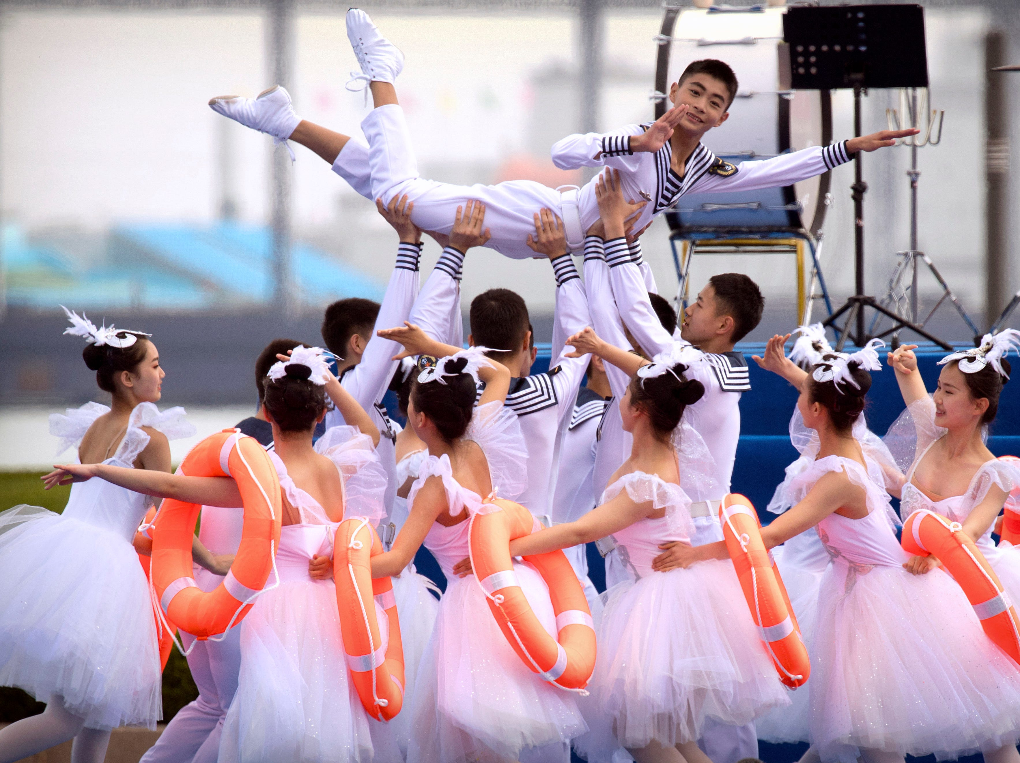A Chinese military dance troupe performs during a concert featuring Chinese and foreign military bands in Qingdao, Monday, April 22, 2019. Ships from Chinese and foreign navies have gathered in Qingdao for events this week, including a naval parade, to mark the 70th anniversary of the founding of the People's Liberation Army (PLA) Navy.