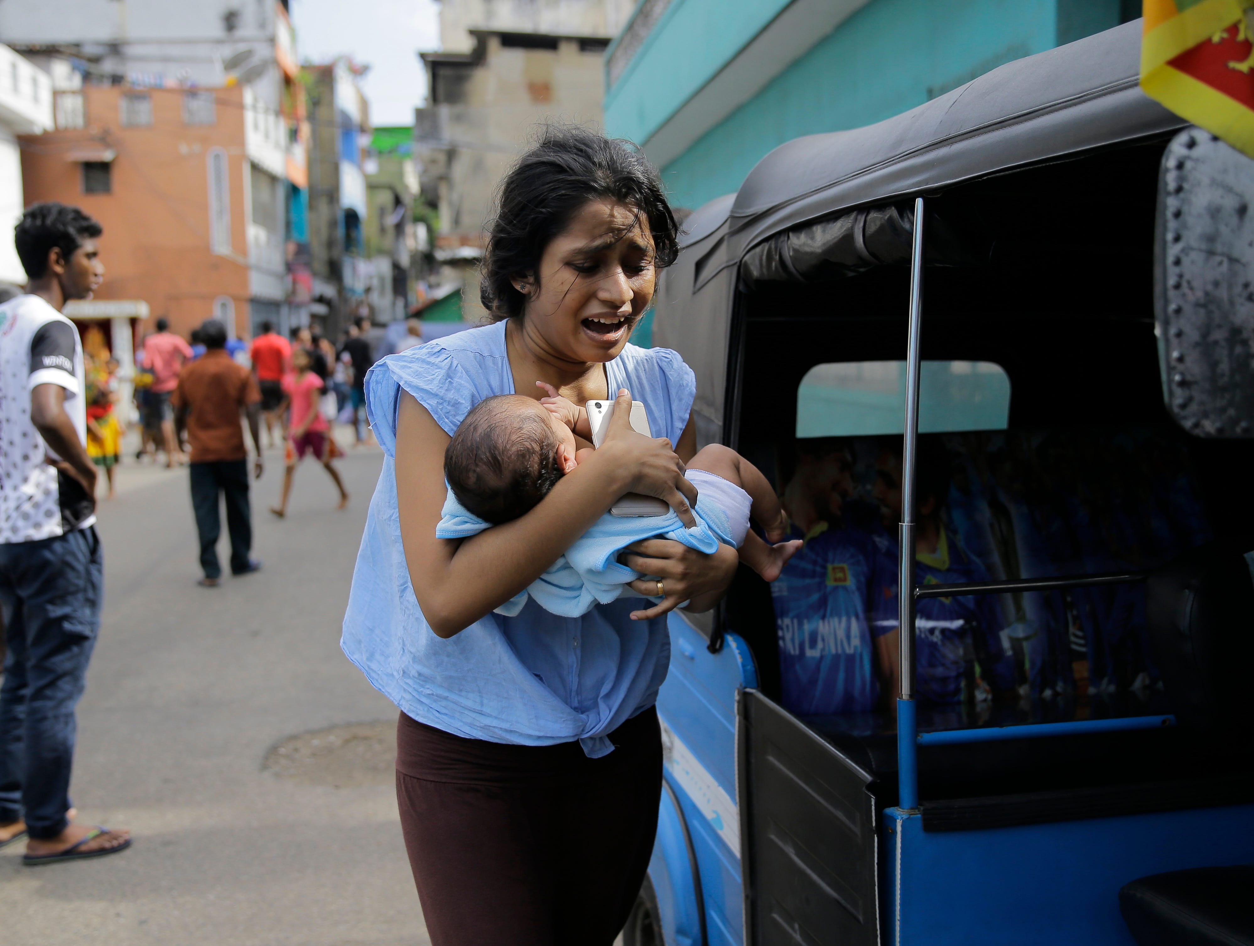 A Sri Lankan woman living near St. Anthony's shrine runs for safety with her infant after police found explosive devices in a parked vehicle in Colombo, Sri Lanka, Monday, April 22, 2019. Easter Sunday bombings that ripped through churches and luxury hotels killed more than 200 people.
