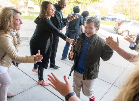 Lodge Elementary sixth-grader Schafer Betts, middle, receives high-fives from volunteers as he enters school for the first day of the three-week iLearn standardized testing Monday morning, April 22, 2019. Young and Established started handing out high-fives a few years ago as a way to encourage students before testing commenced.