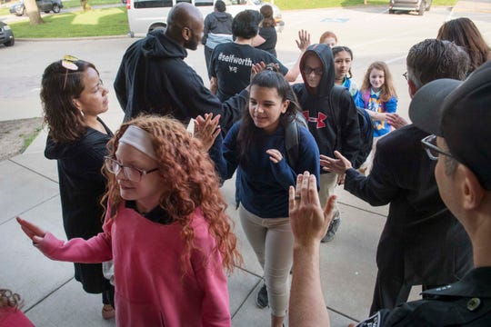 Lodge Elementary students receive high-fives from volunteers as they enter school for the first day of their three-week iLearn standardized testing Monday morning, April 22, 2019. Young and Established started handing out high-fives a few years ago as a way to encourage students before testing commenced.
