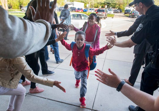 Lodge Elementary third-grader Damien Armstead receives high-fives from volunteers as he enters school for the first day of their three-week iLearn standardized testing Monday morning, April 22, 2019. Young and Established started handing out high-fives a few years ago as a way to encourage students before testing commenced.