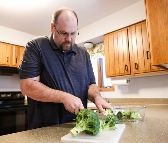 Matt Moore of Fond du Lac prepares food April 20, 2019, in his home in Fond du Lac, Wis. He changed his lifestyle after suffering a severe stroke in November at the age of 43.