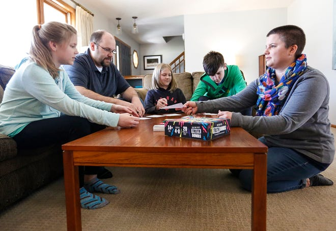 Matt Moore (second from left) plays a board game with his family April 20, 2019, in their Fond du Lac, Wis., home. From left to right are, Molly, Matt, Allison, Everett and Jackie. Life-saving measures taken at Froedtert Hospital in Milwaukee saved Moore's life after he suffered a severe stroke last year at the age of 43.