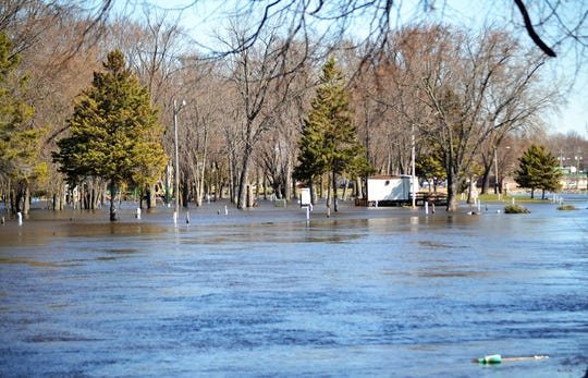 The flooded Oconto River and Holtwood Park and Campground are seen from Pecor Street on Friday.