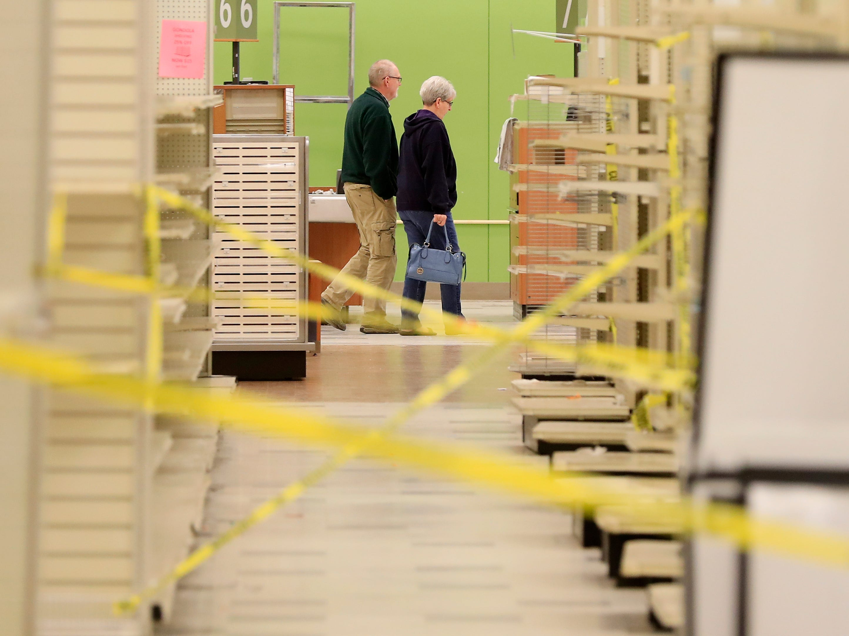 Customers walk past empty aisles on the final day of business at the Shopko store on Military Avenue in Green Bay. The store was the company's first.